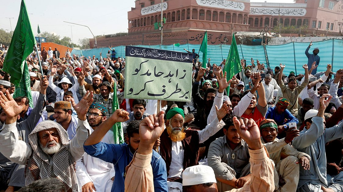 "A supporter of the Tehreek-e-Labaik Pakistan, an Islamist political party, holds a sign, which reads in Urdu, ""remove Zahid Hamid"" during a sit-in protest along a main road in Karachi"